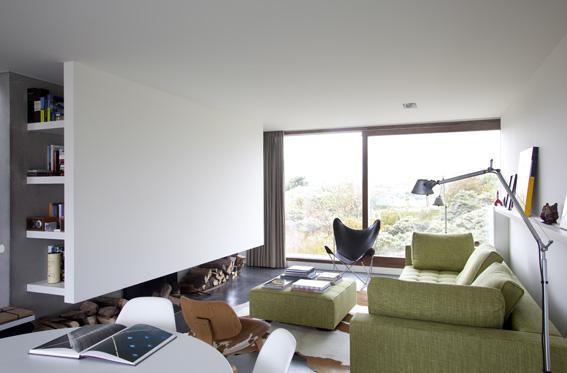 бельгийский минимализм - встроенные полки и дрова в белой гостиной
