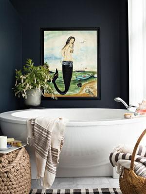 Белая круглая ванна, темно-серая стена и картина в маленькой ванной