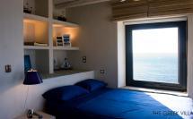 греческие интерьеры - спальня полками в изголовье кровати и синим покрывалом
